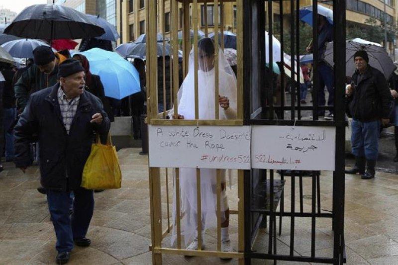 黎巴嫩首都貝魯特街頭,人權團體阿巴德(ABAAD)成員身著白紗,手纏繃帶,站在金色的牢籠中,籠外掛著的標語寫著「白紗並不能遮掩強暴的事實(AP)