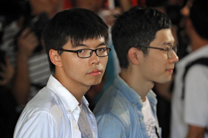 香港「雙學三子」黃之鋒(左)、羅冠聰(右)及周永康3年前發起衝擊「公民廣場」,開啟雨傘運動。2017年8月17日,3人遭判刑入獄,黃之鋒半年、羅冠聰8個月、周永康7個月。(AP)
