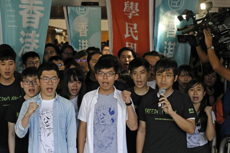 香港「雙學三子」黃之鋒(中)、羅冠聰(左)及周永康(右)3年前發起衝擊「公民廣場」,開啟雨傘運動。2017年8月17日,3人遭判刑入獄,黃之鋒半年、羅冠聰8個月、周永康7個月。(AP)