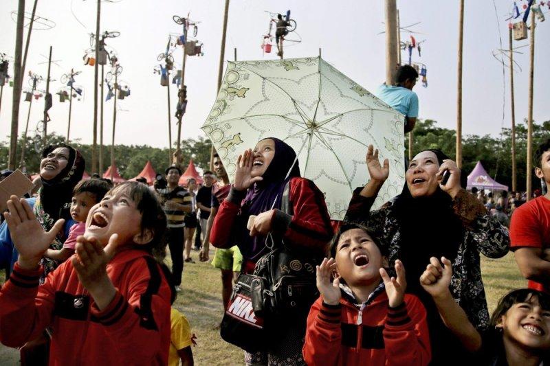 爬檳榔樹比賽的參賽者親友吶喊加油(AP)