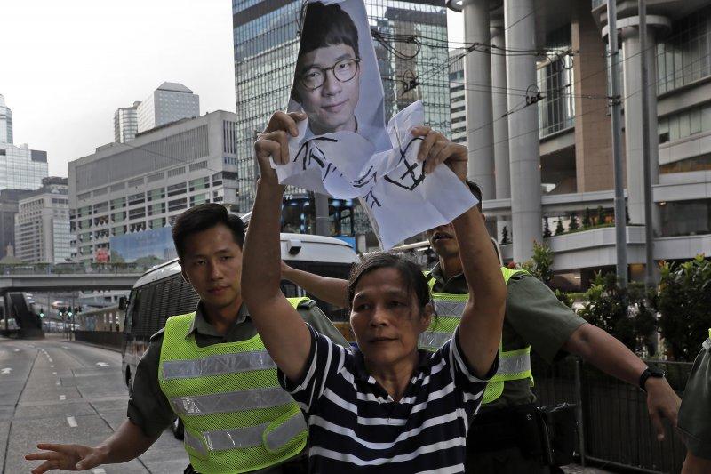 香港青年世代政治領袖黃之鋒、羅冠聰、周永康遭判刑入獄,支持者激動抗議(AP)