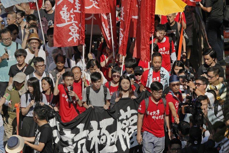 大批香港民眾20日上街遊行,高喊釋放政治犯、良心犯等口號,聲援遭判刑入獄的青年世代政治領袖黃之鋒、羅冠聰與周永康。(美聯社)