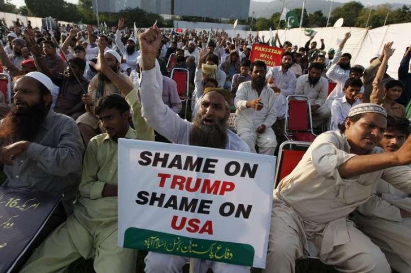 巴基斯坦反美民眾27日在街頭抗議,舉「川普可恥、美國可恥」的標語。(AP)
