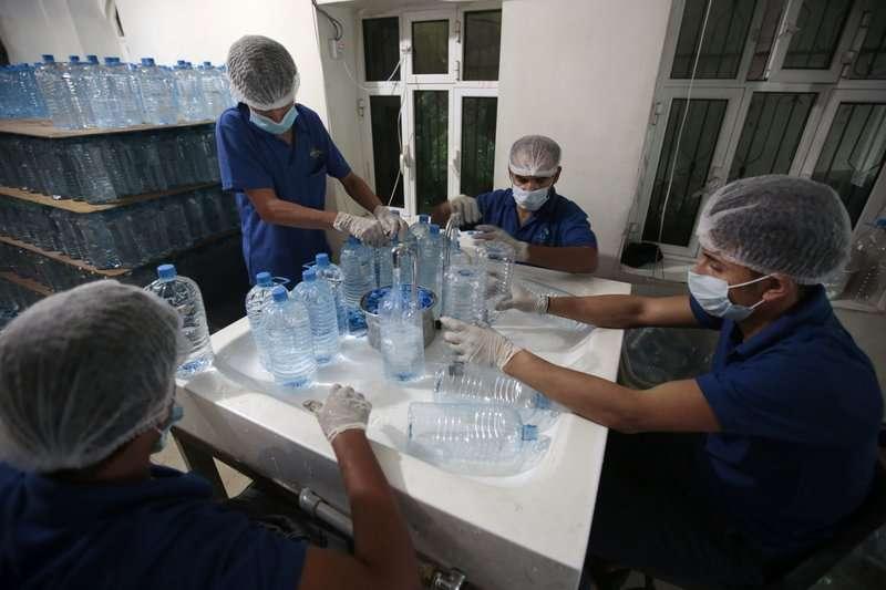 葉門首都沙那的衛生人員正在裝乾淨的礦泉水。(AP)