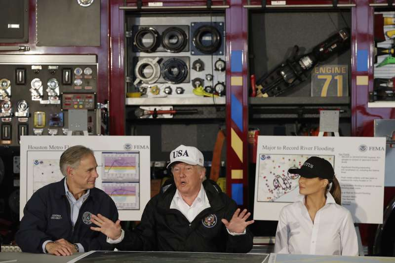 美國總統川普(中)與第一夫人梅蘭妮亞(右)聽取德州州長艾伯特的風災報告。(AP)