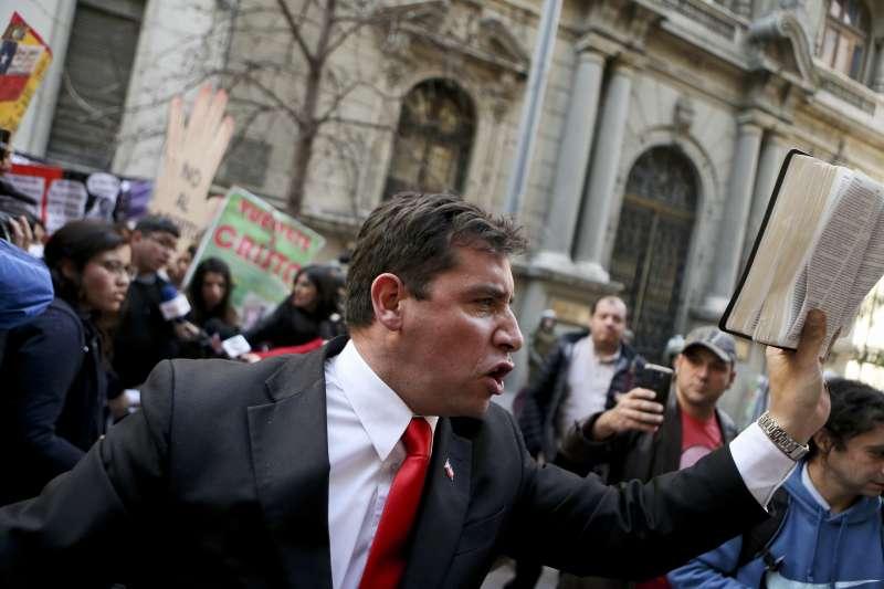 智利的保守天主教人士拿著聖經抗議。(美聯社)