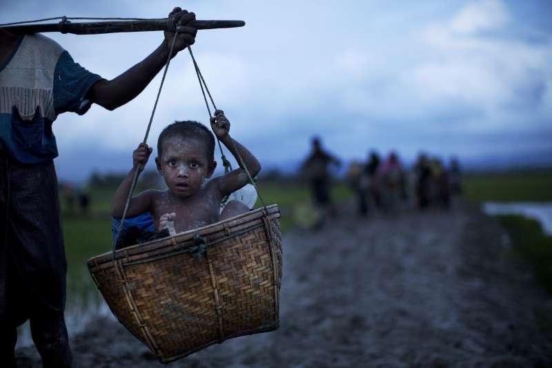 羅興亞難民挑著自己的孩子,徒步逃往孟加拉。(美聯社)