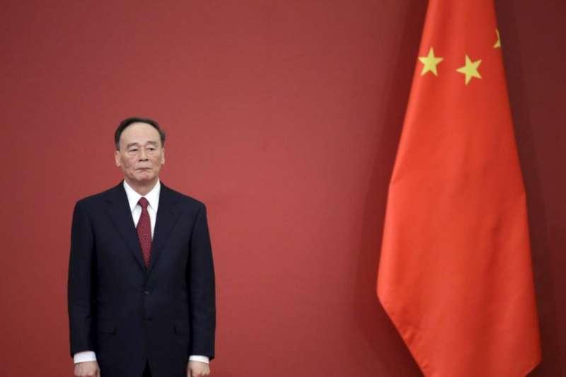 中共中央政治局常委,中紀委書記王岐山在北京人民大會堂站在國旗旁(資料照,美國之音)