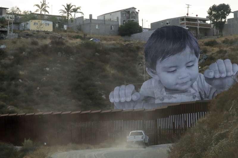 巨大的男孩正大光明的在美墨邊境牆上偷看美國,來自法國藝術家JR的作品,適逢川普政府欲取消「逐夢者計畫」,引來國際關注。(AP)