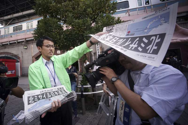 日本媒體在街頭發送號外,通報北韓發射飛彈的最新消息。(美聯社)