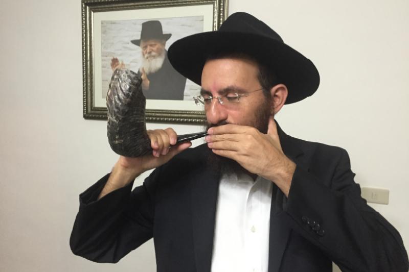 吹號角是猶太新年中最重要的儀式,圖為台北市可巴德猶太協會拉比示範吹號角(台北市可巴德猶太協會提供)