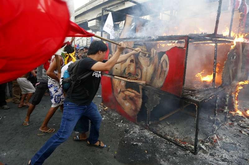 示威民眾焚燒杜特蒂和馬可仕的畫像。(美聯社)