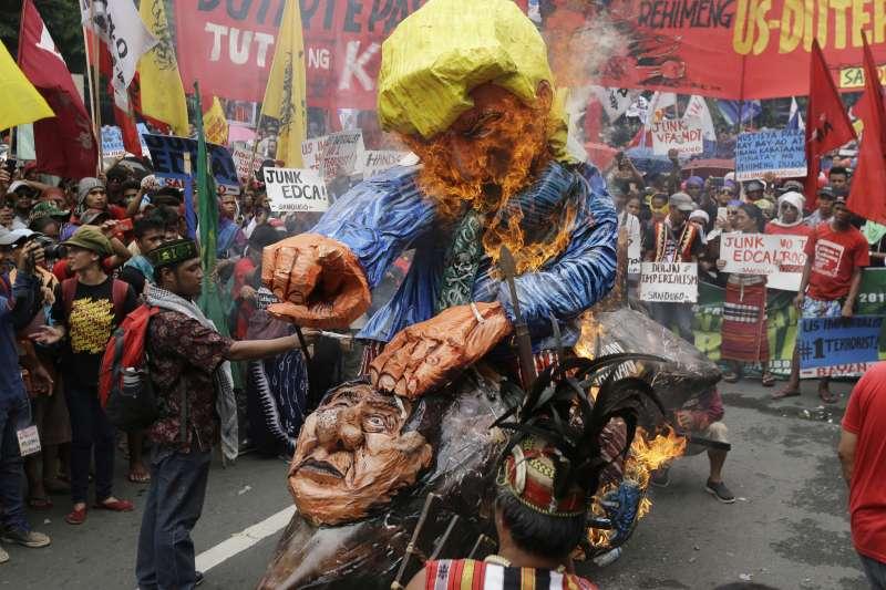 騎著「杜特蒂火箭」的川普肖像,出現在菲律賓的反獨裁遊行。(美聯社)