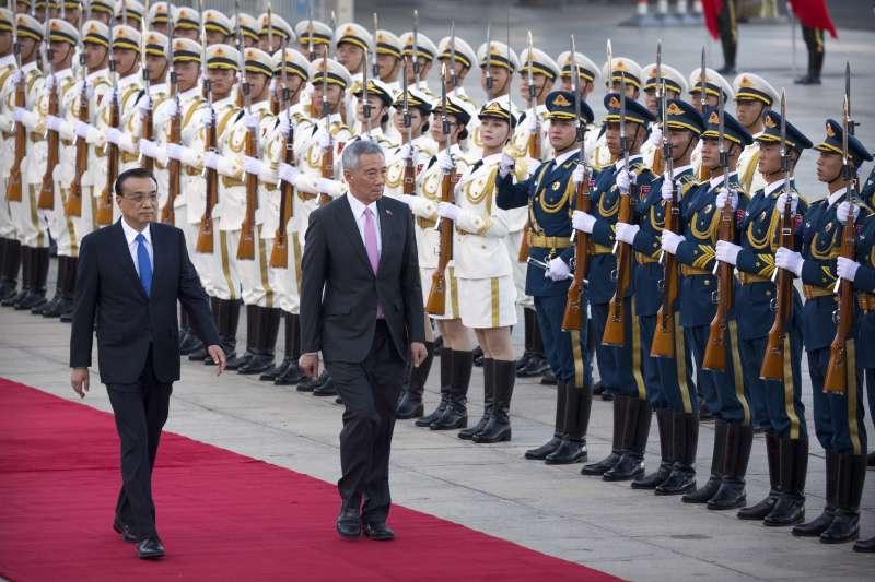 新加坡總理李顯龍在中國國務院總理李克強陪同下檢閱儀仗隊。(美聯社)
