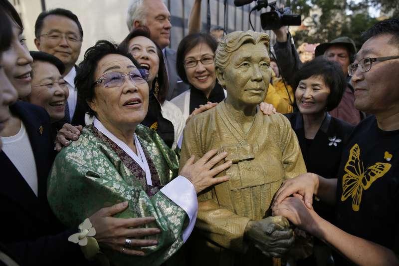 南韓訂定8月14日為慰安婦紀念日,圖為曾被迫當慰安婦的李容洙與美國舊金山慰安婦銅像合影(AP)