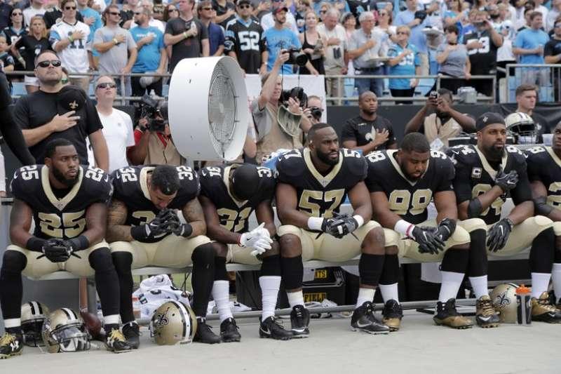 NFL紐澳良聖徒球員24日在國歌演奏時坐在板凳上,抗議川普對運動員不友善的言論。(AP)