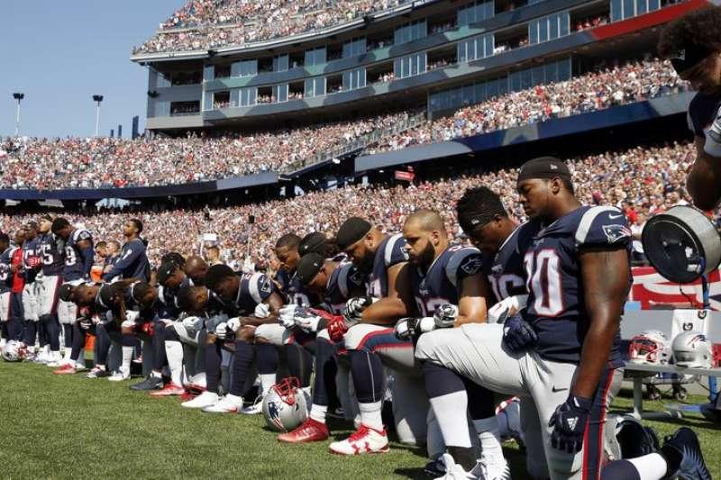 NFL新英格蘭愛國者24日出戰休士頓德州人,多名球員在國歌演奏時單膝下跪,抗議川普對運動員不友善的言論。(AP)