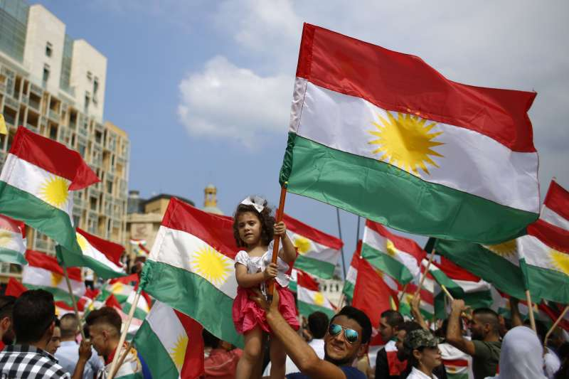 伊拉克庫德族獨立公投,庫德民眾持旗幟上街歡迎。(美聯社)