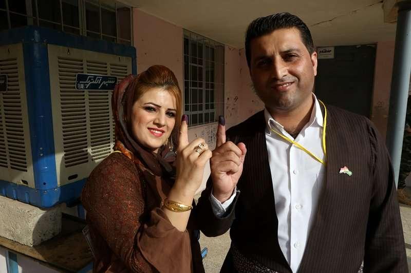 伊拉克庫德族獨立公投,一對男女展示投票的手指印痕。(美聯社)