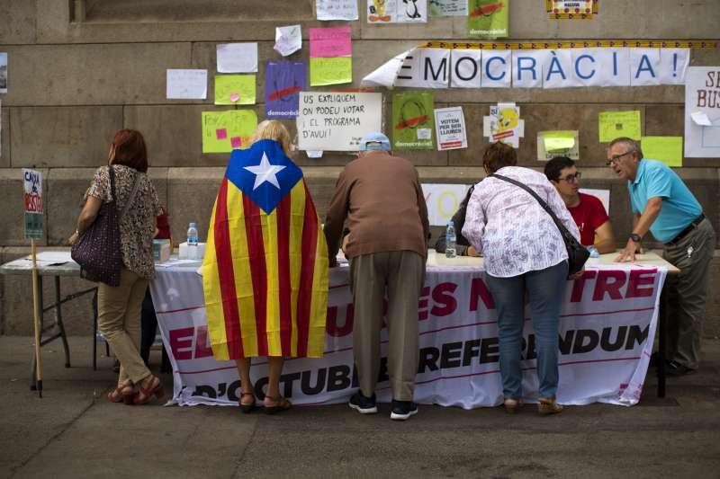 9月25日,加泰隆尼亞首府巴塞隆納的一所大學的學生擺攤,告知民眾關於投票所的資訊(AP)