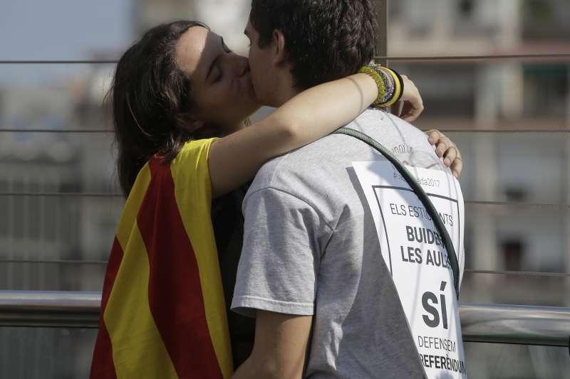 西班牙加泰隆尼亞自治區10月1日舉行獨立公投前夕,支持者不斷上街抗議中央政府打壓,一對情侶抗議不忘擁吻(AP)