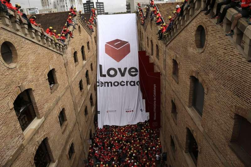 西班牙加泰隆尼亞自治區10月1日舉行獨立公投前夕,支持者不斷上街抗議中央政府打壓,連消防員也爬上屋頂,放下一幅繪有投票箱的旗幟表態(AP)
