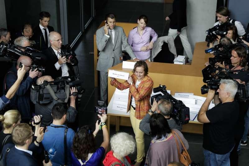 德國另類選擇黨(AfD)第一次進入國會,一名議員開心亮出名條。(美聯社)