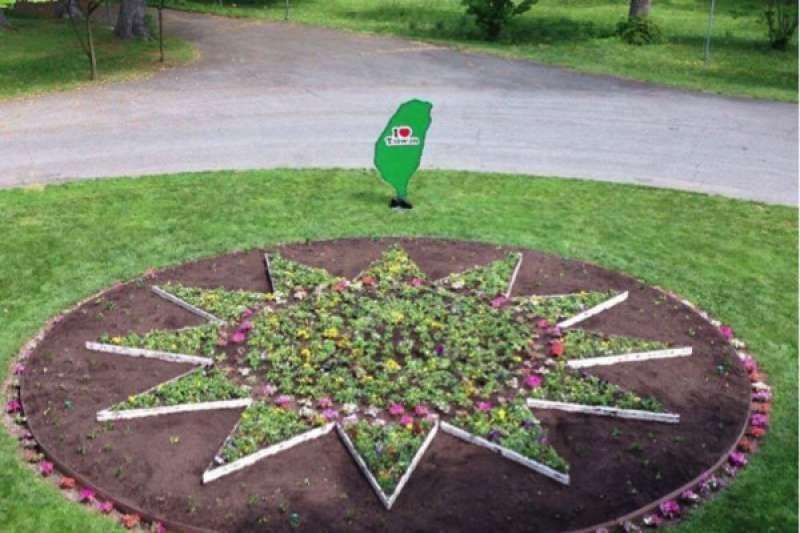 外交部長李大維指示駐美代表處更改雙橡園造景,將國徽中「青天」部分的花草移除、留下「白日」部分種植綠色植栽,綠色「我愛台灣」立牌移到國徽旁。(外交部提供)