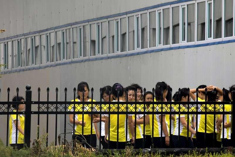 於海鮮加工廠的北韓勞工整隊集合 。(美聯社)