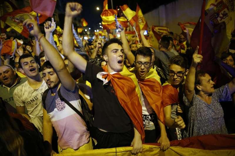 反加獨的民眾在巴賽隆納街頭身披西班牙國旗、振臂高呼。(美聯社)