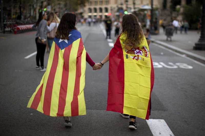 西班牙東北部加泰隆尼亞自治區獨立公投之後,與馬德里中央政府劍拔弩張,不過兩個各披著加泰隆尼亞孤星旗(左)與西班牙國旗的小女孩,還是可以牽手回家(AP)