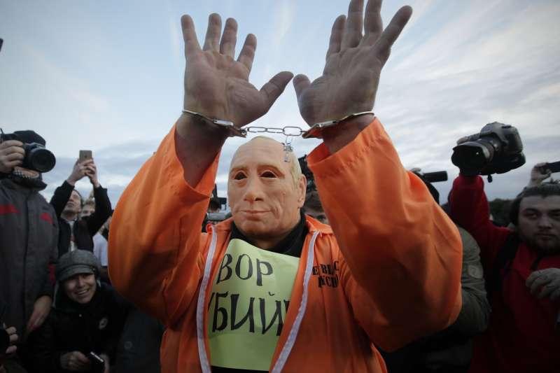普京生日示威:抗議民眾扮成普京被上手銬的樣子(AP)