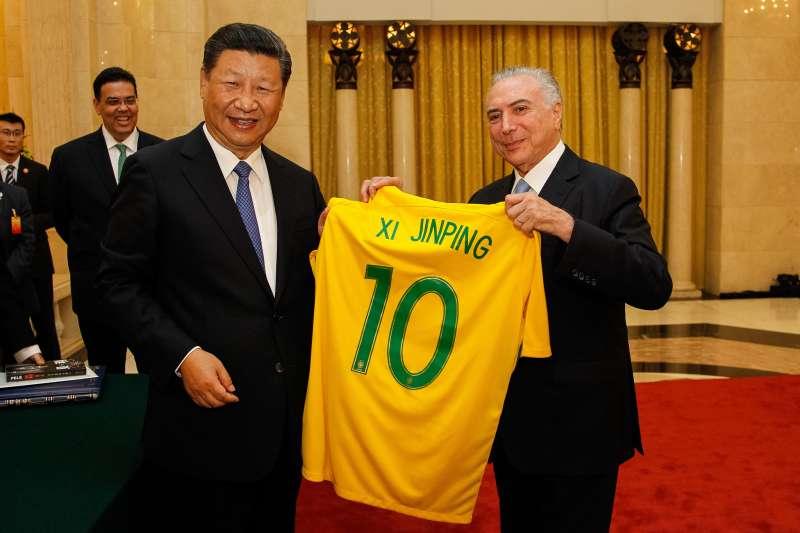 隨著世界兩大經濟體中國和美國在貿易問題上角力,中國已日益寄望巴西填補空缺,在巴西進行了多角化投資。圖為巴西總統特梅爾(Michel Miguel Elias Temer Lulia)贈送印有中國主席習近平印有其名字的球衣。(資料照,Michel Temer@flickr提供)