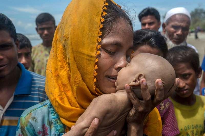 一名逃往孟加拉的羅興亞難民手中捧著在船難中喪生的孩子。(美聯社)