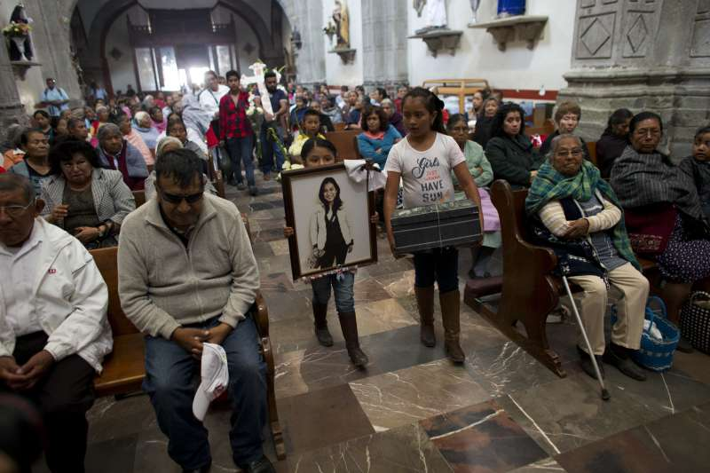 墨西哥針對女性的暴力犯罪日益猖獗,一位受害女醫師的家人拿著遺照與十字架為她哀悼。(美聯社)