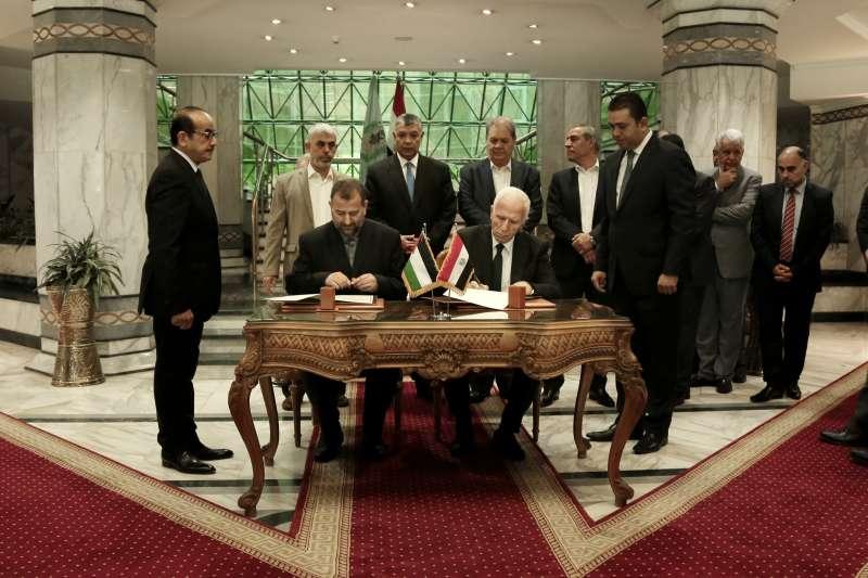 巴勒斯坦大和解:法塔高層阿馬德(Azzam al-Ahmad,中右)與哈瑪斯代表阿洛里(Saleh al-Arouri,中左)簽署協議(AP)