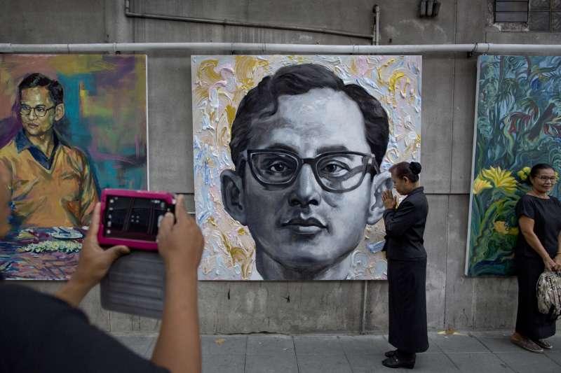 泰國人民拍攝已故泰王蒲美蓬的畫像。(美聯社)