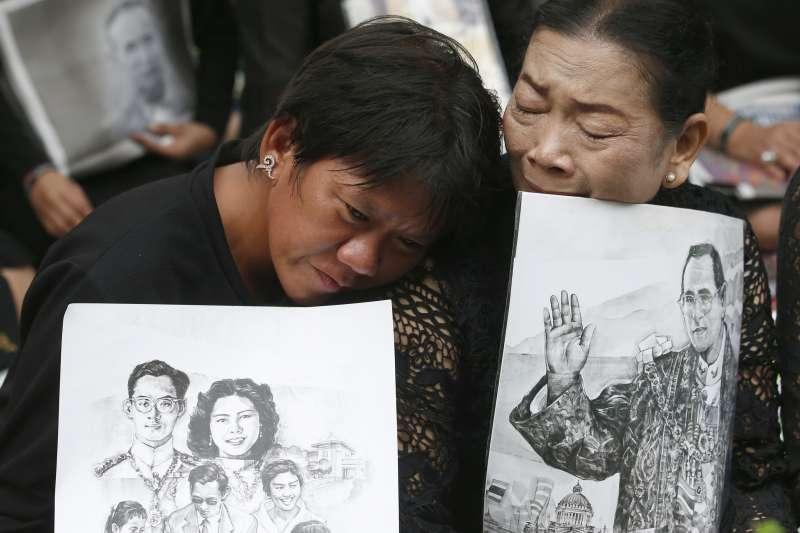 泰王蒲美蓬逝世一周年,泰國民眾手持畫像痛哭哀悼。(美聯社)