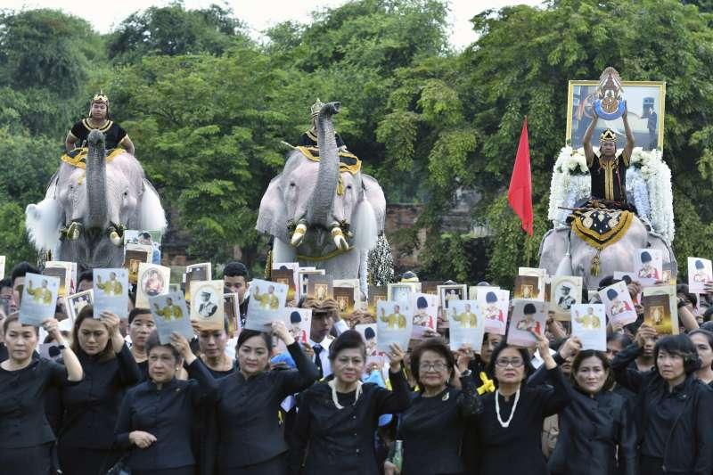 泰王蒲美蓬逝世一周年,大象也被撲上白色粉末,列隊參加哀悼儀式。(美聯社)