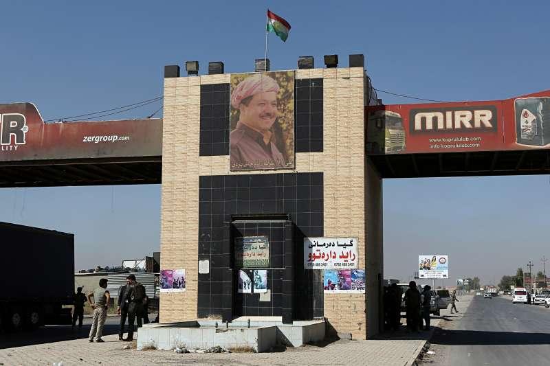 伊拉克庫德自治區首府艾比爾郊外由庫德族部隊駐守的檢查站,牆上掛著自治政府主席巴爾札尼海報(AP)