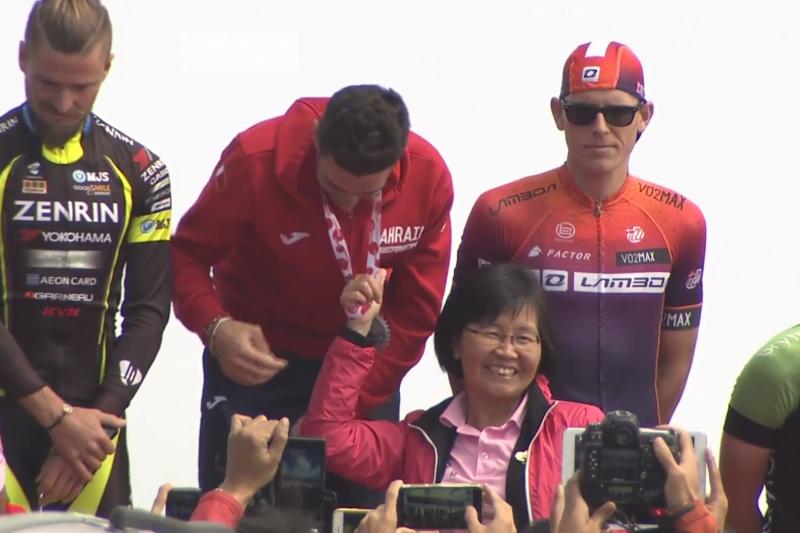頒獎人陳淑慧為了合影,單手扯著掛在義大利選手尼巴利脖子上的獎牌,讓尼巴利僅能彎腰合照。(取自民視轉播)