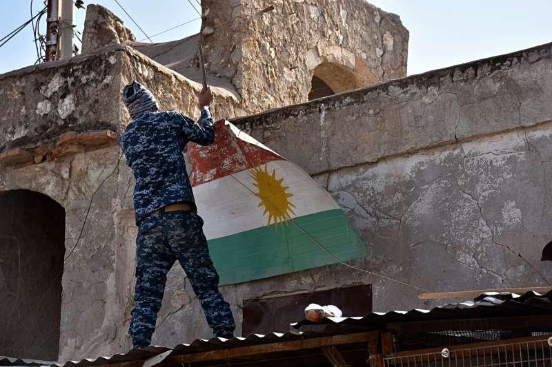 伊拉克軍隊拿下庫德族佔領的石油大城基爾庫克,圖為伊拉克軍人摘下庫德族旗幟。(美聯社)