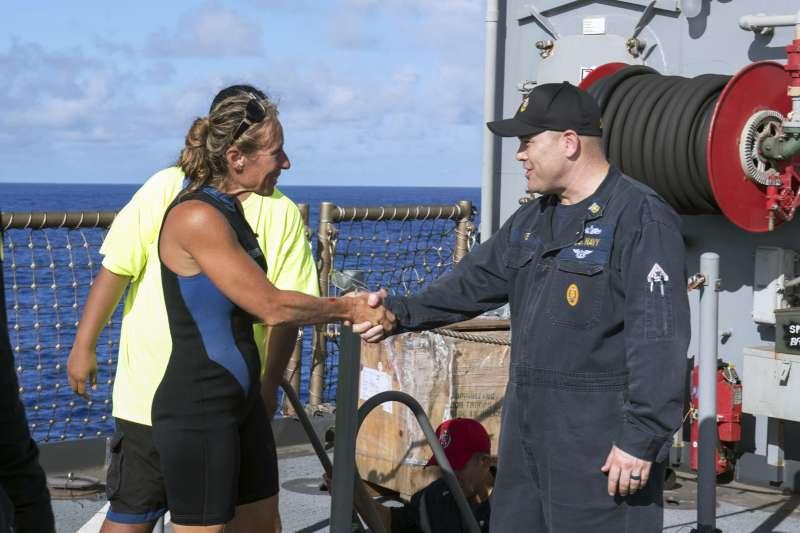 獲救的美國女子愛沛兒登上美軍船艦,與艦長握手。(美聯社)