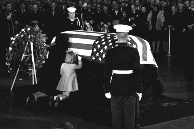 1963年11月24日,美國國會大廈圓形大廳內,甘迺迪遺孀賈桂琳悲傷地親吻甘迺迪的靈柩,甘迺迪的女兒卡洛琳跪在一旁(AP)