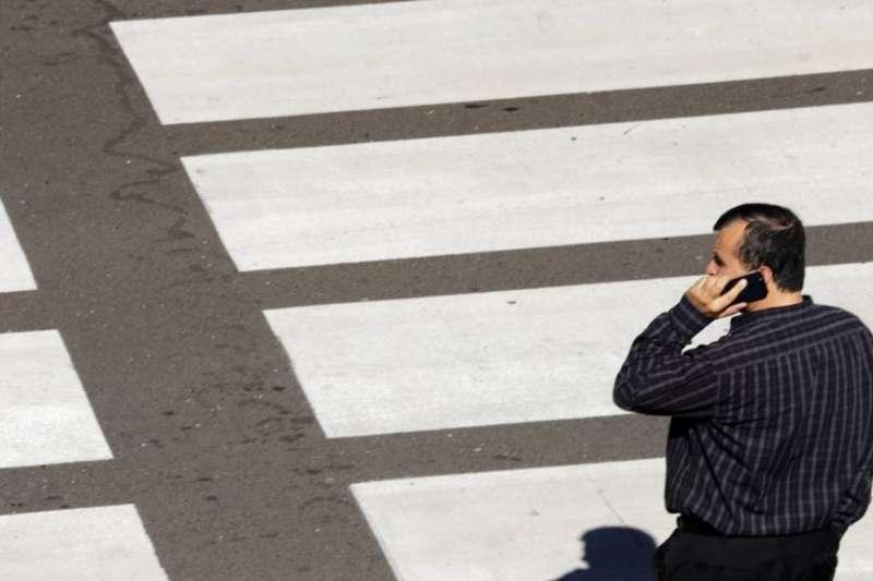 一位過馬路打手機的男士。(美國之音)