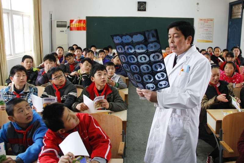 2016年3月23日,在中國安徽省全椒縣大墅鎮小學,一名醫生結合肺結核病人的胸片向孩子們介紹結核病相關知識。(新華社)