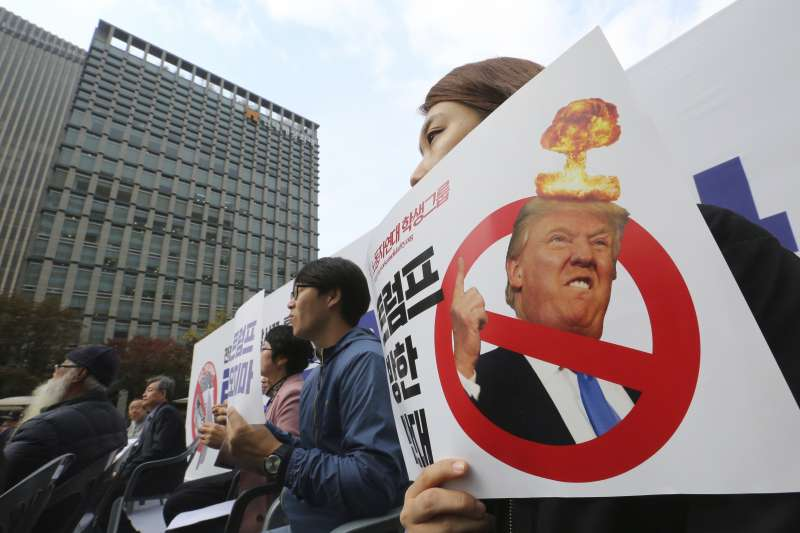 南韓青瓦台外聚集抗議川普的民眾,手上高舉標語「我們反對川普訪韓」。(美聯社)