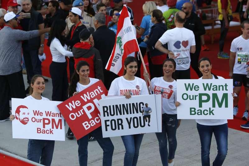 黎巴嫩民眾高舉標語聲援總理哈里里,期盼他盡快回國。(美聯社)