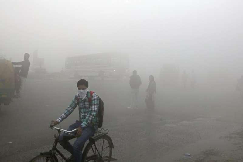 印度首都新德里空汙嚴重,當地人民用口罩遮掩口鼻。(美聯社)