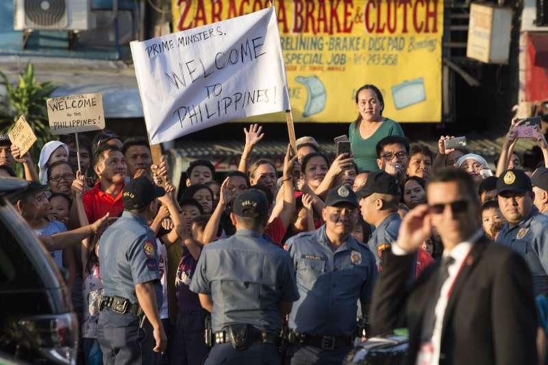 上百位民眾在Jollibee外,還有人舉著臨時製作的旗子歡迎杜魯道。(美聯社)